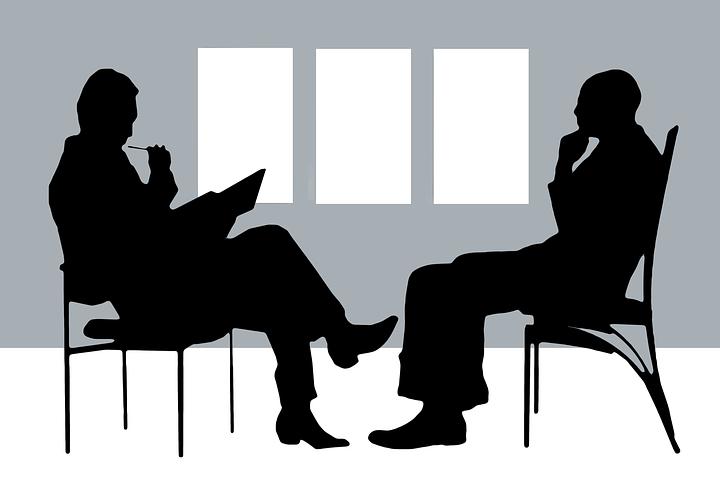 2 Personen sitzen sich in Beratungssituation gegenüber