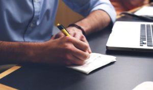 Hand schreibt auf Papier_